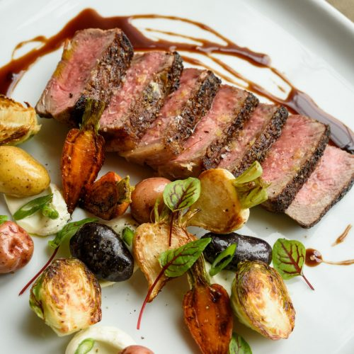 beef-striploin-with-confit-potato-scallion-clabber-cream-charred-vegetables-and-tarragon-jus-scaled